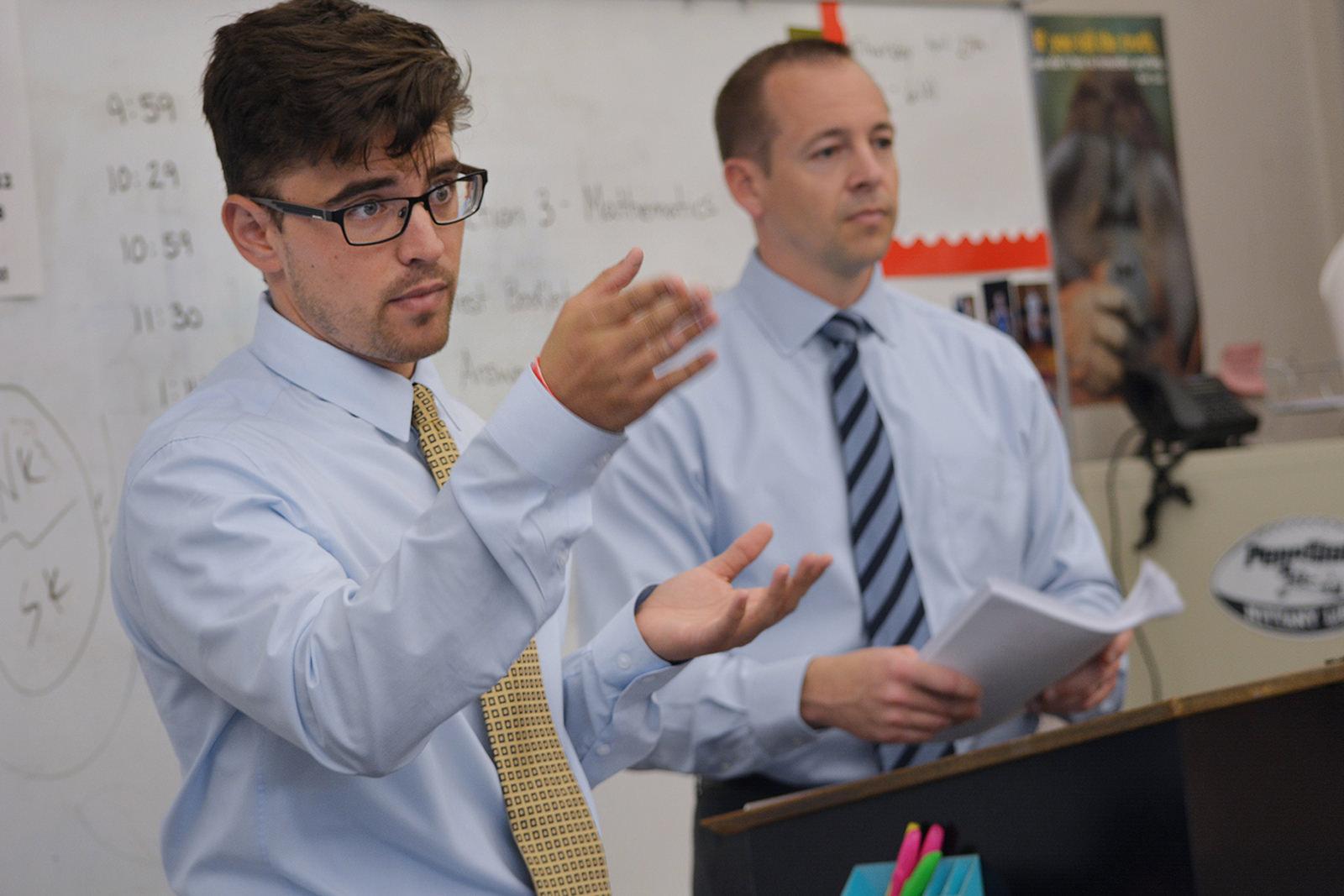 twee docenten die samen voor de klas staan