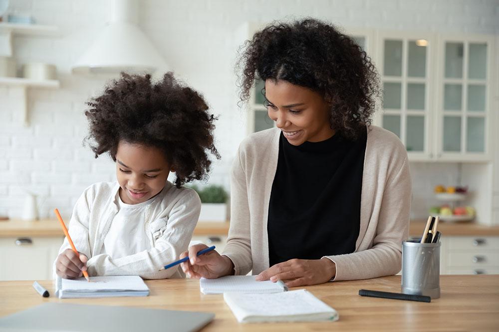 Ouder helpt kind met huiswerk